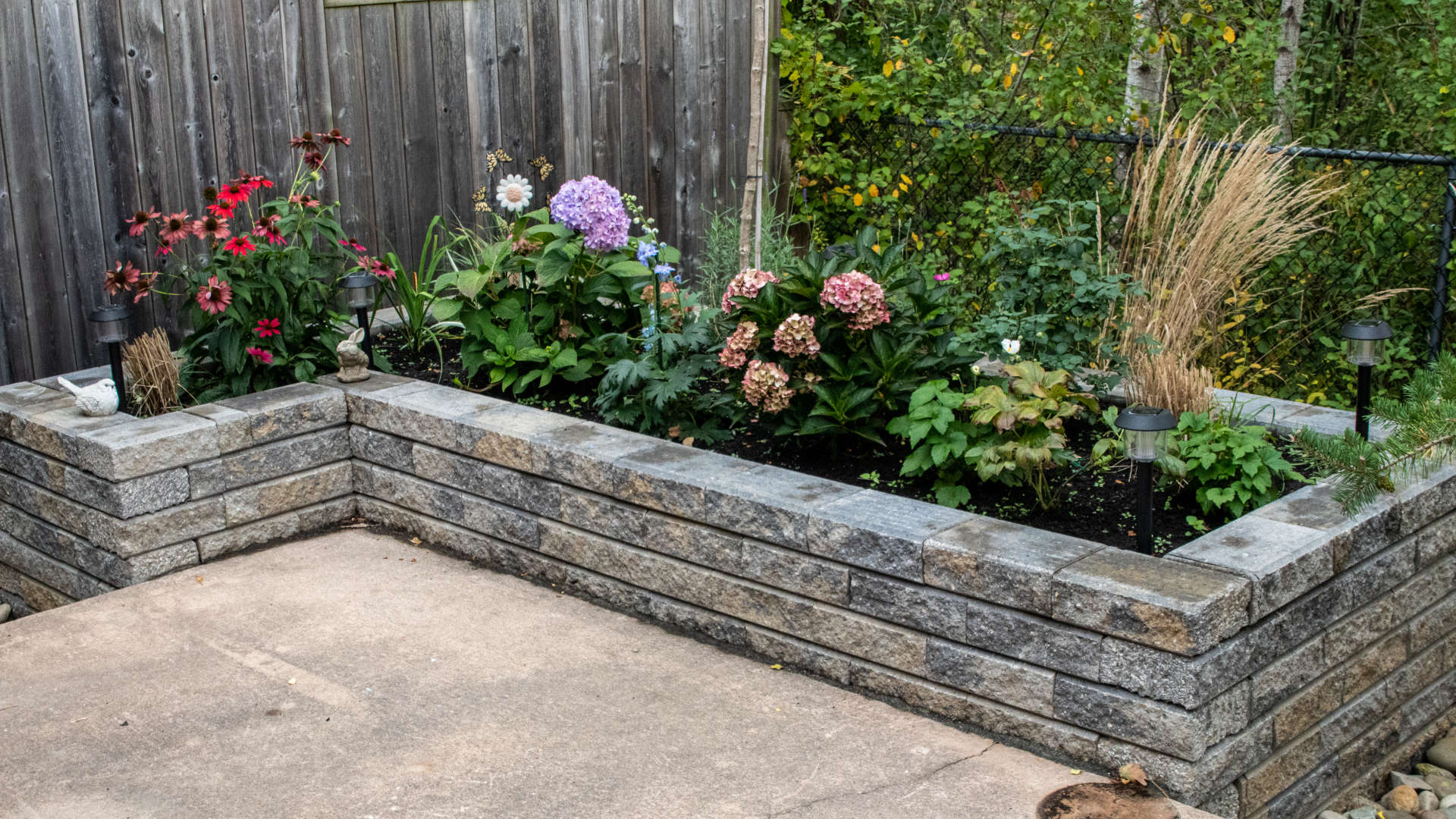 Landscaping, hardscaping and stonework project London Ontario. Stone retaining wall flower bed.