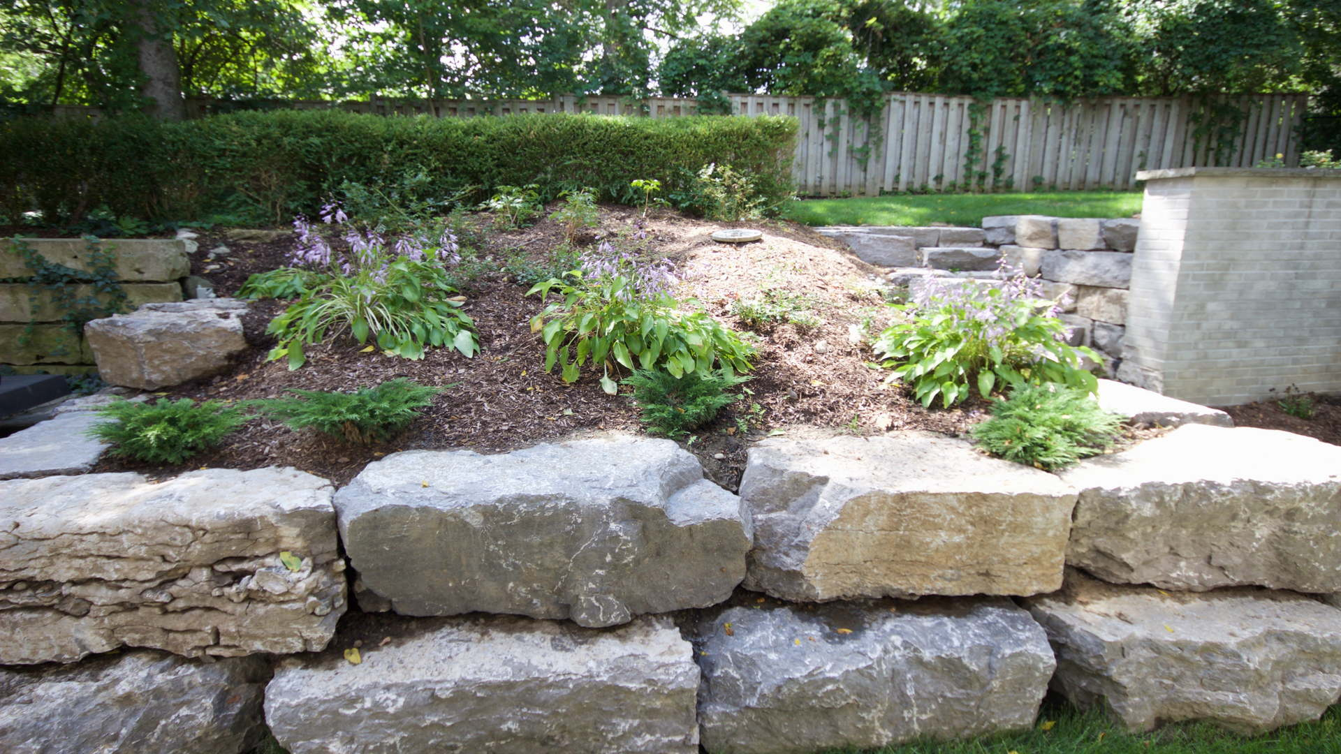 Natural garden with large armour stone retaining wall, various hostas and pine mulch. Traditional landscaping / hardscaping project in London Ontario.