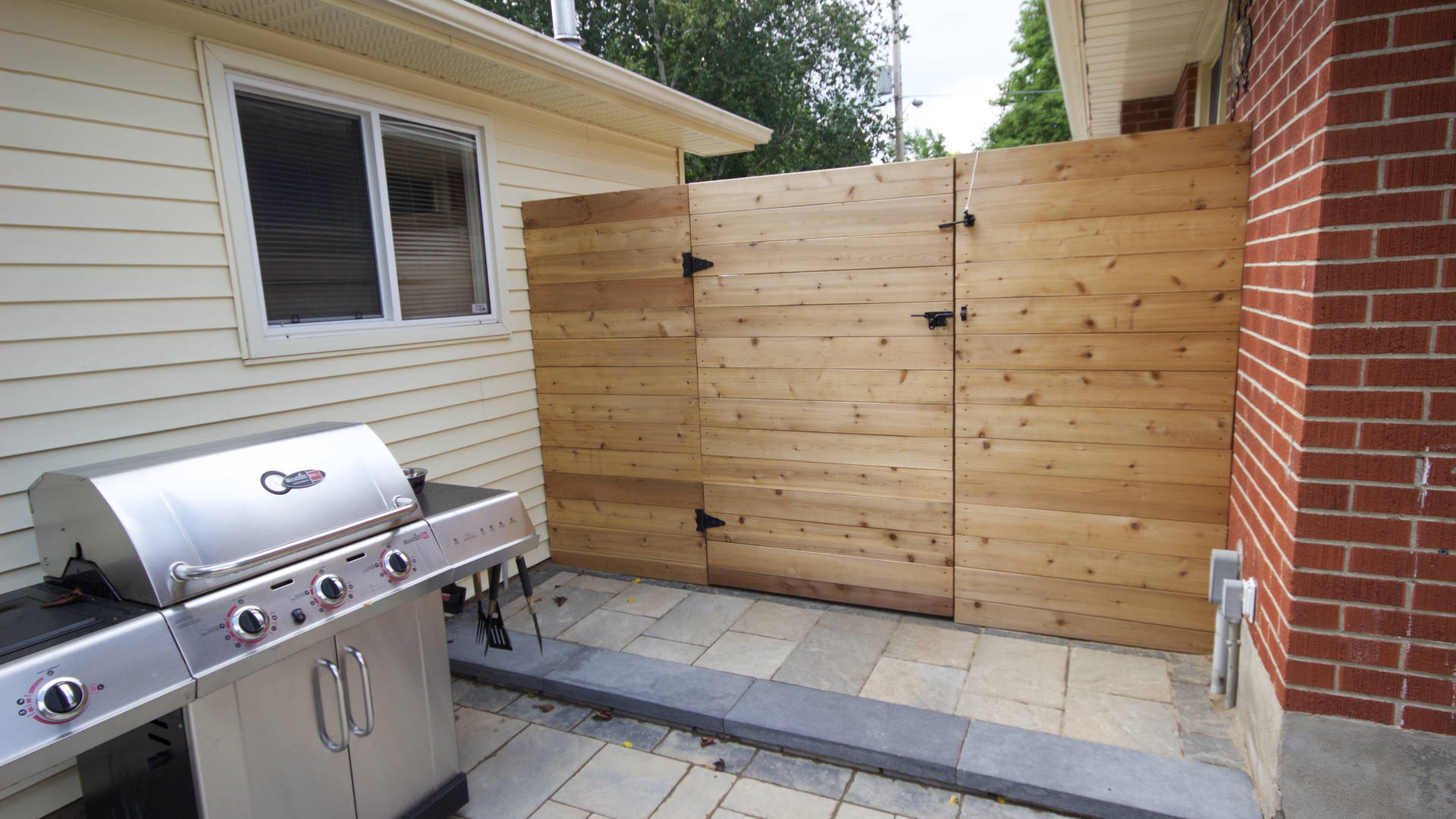 Small cooking area complete with a modern, horizontal fence and gate, and an interlock patio made up of large, pre-fabricated stones for the barbecue to rest on. Modern hardscaping and woodwork project in London Ontario.