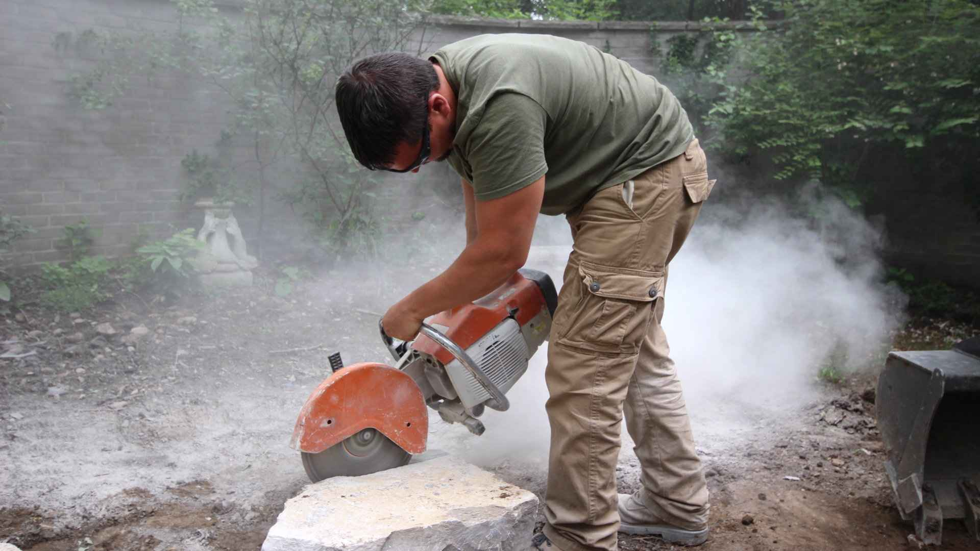 Landscape installation, construction and hardscaping: Nate of Old South Landscape Professionals cutting stone.